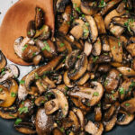 Sautéed mushrooms in a skillet with a wood serving spoon, garnished with chopped fresh herbs.