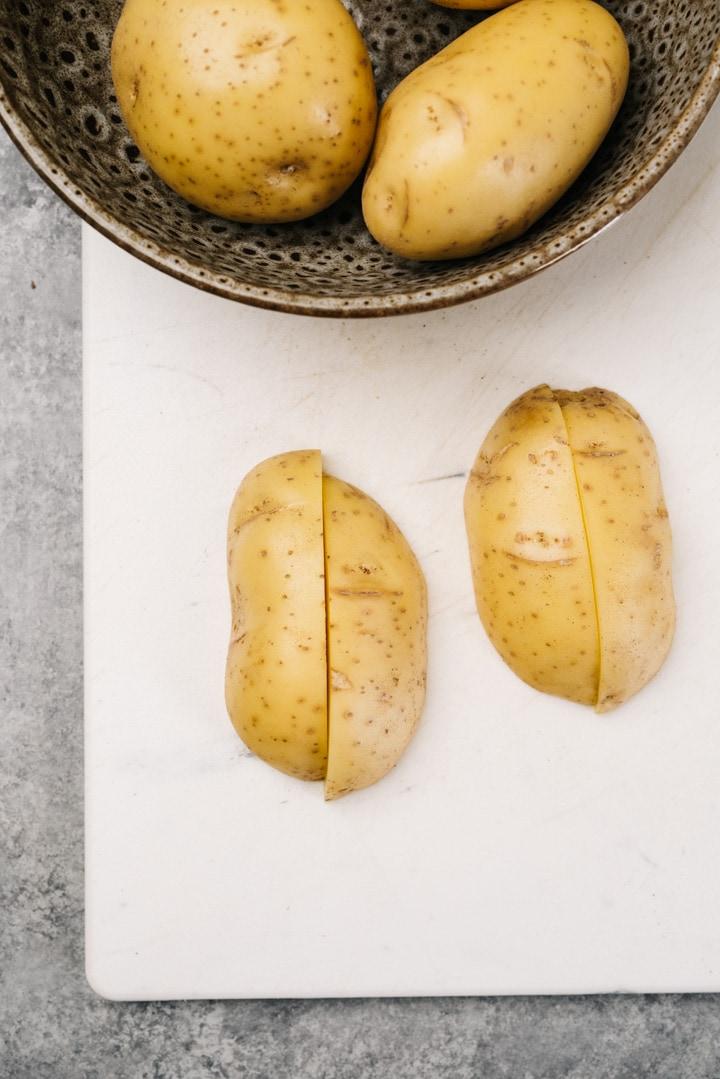 A yukon gold potato sliced into quarters on a cutting board.
