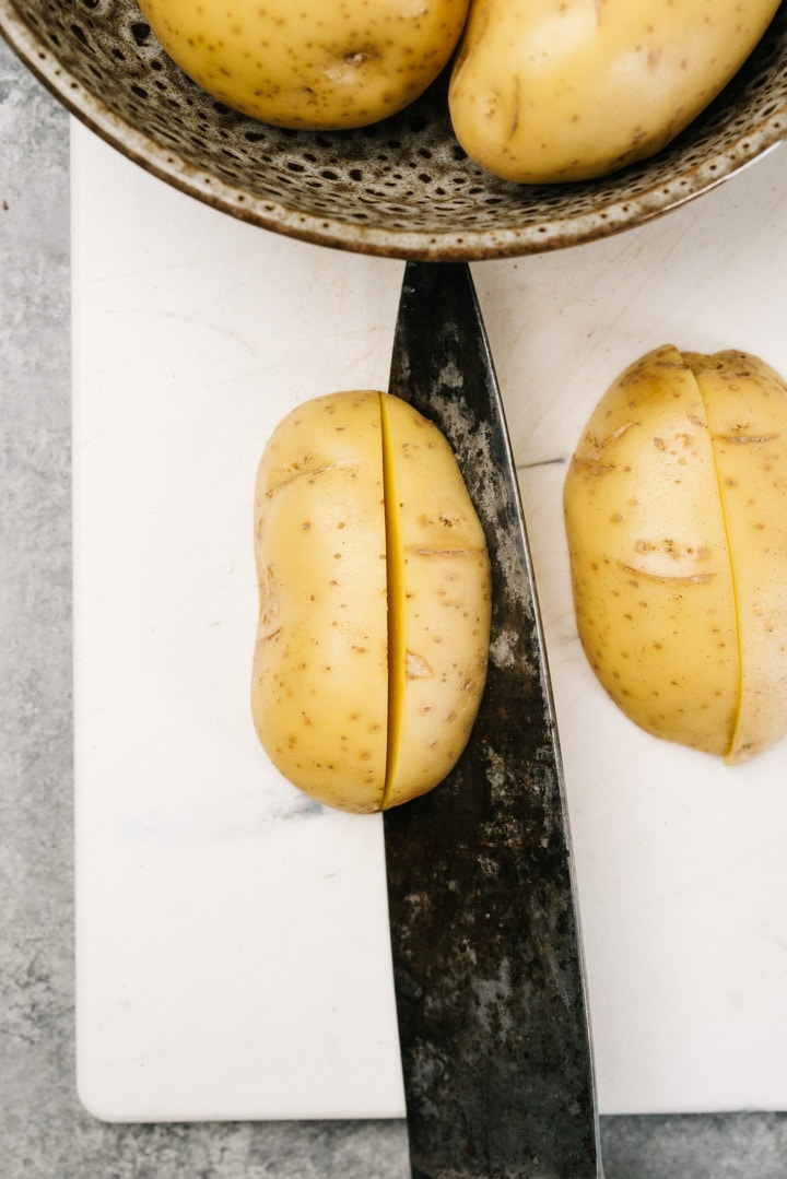 A knife slicing potatoes into quarters (wedges) on a white cutting board.