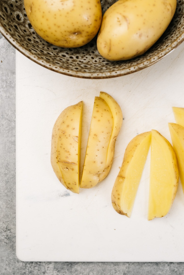 A yukon gold potato sliced into wedges on a white cutting board.