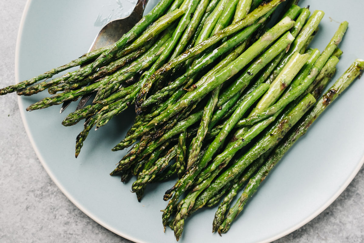 Grilled asparagus spears on a blue serving plate on a concrete background.