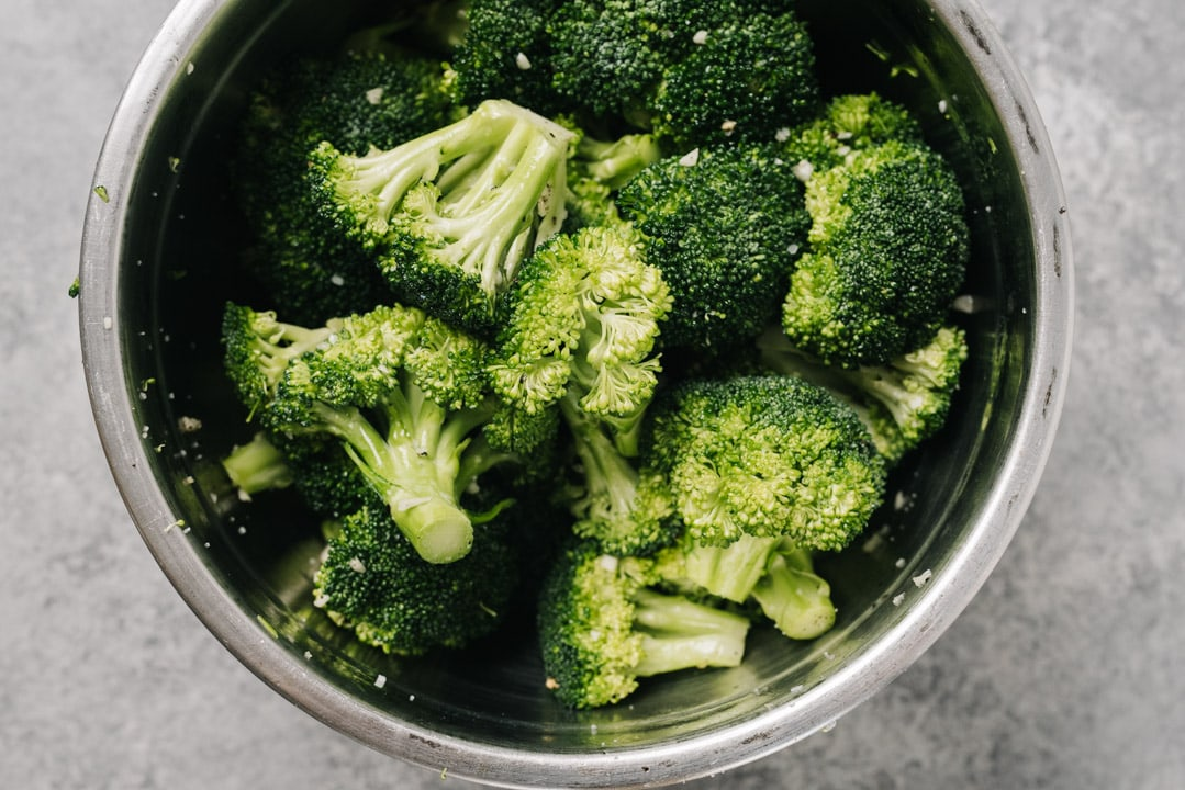 Raw broccoli florets tossed with olive oil and seasoning in a metal mixing bowl.