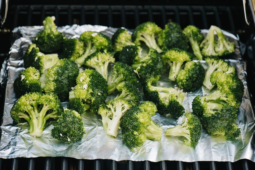 Broccoli florets grilling over a piece of foil.