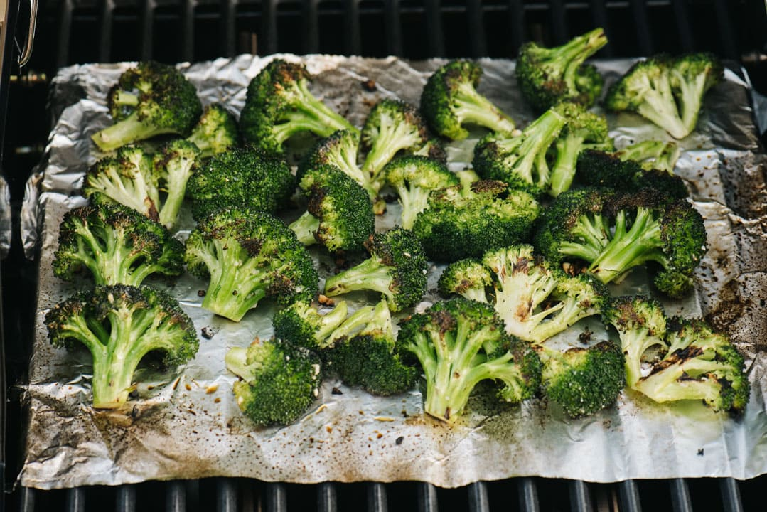 Grilled broccoli florets with a piece of foil between the grill grates and the broccoli.
