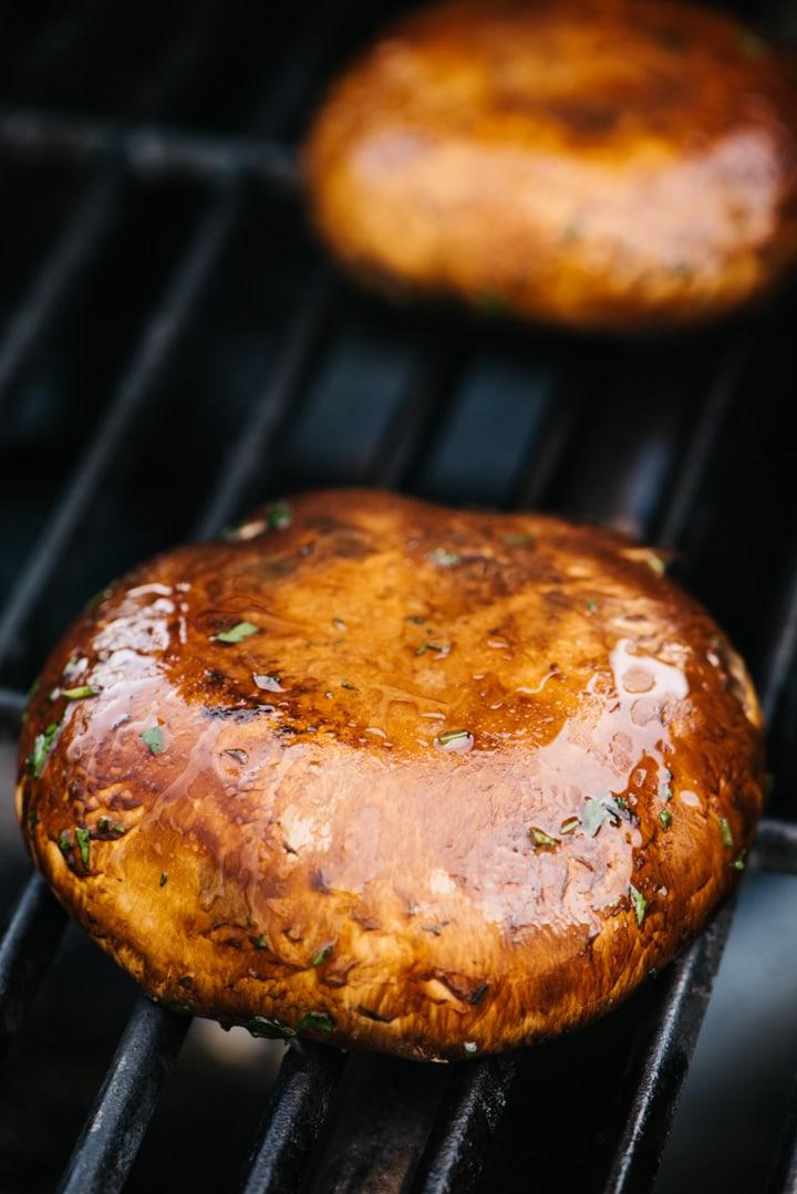 Two portobello mushroom caps gill side down on a gas grill.