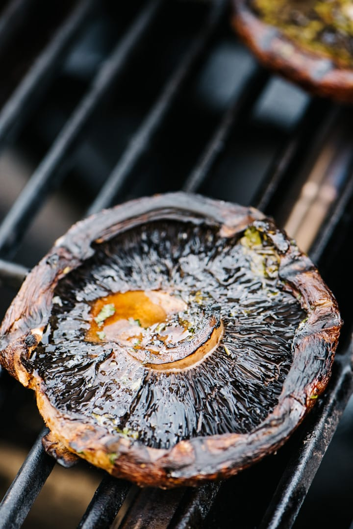 Two portobello mushrooms gill side up, cooking on a gas grill.
