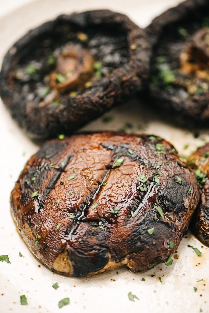 Four grilled portobello mushroom caps on a tan speckled plate, garnished with fresh herbs.