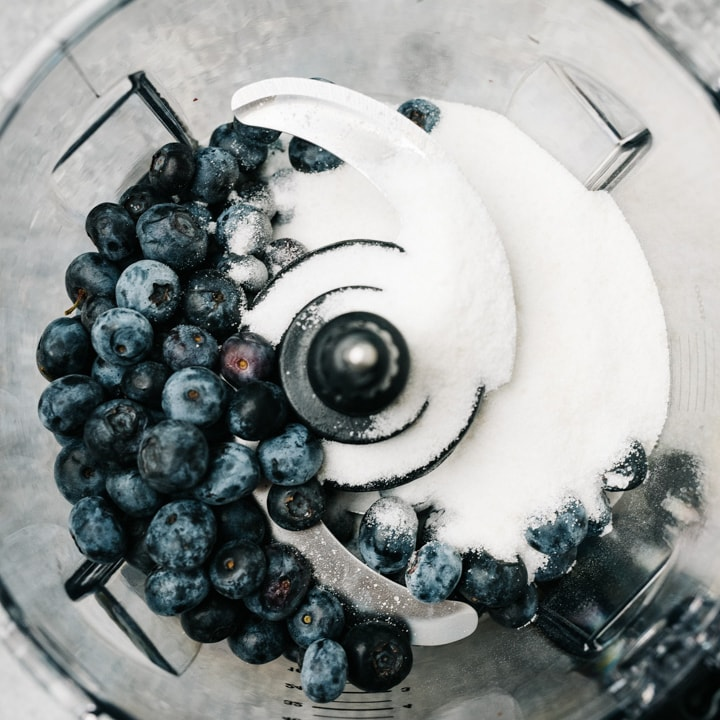 Blueberries and sugar in the bowl of a blender.