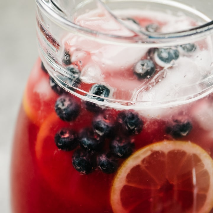 A pitcher of homemade blueberry lemonade garnished with lemon wheels and fresh blueberries.