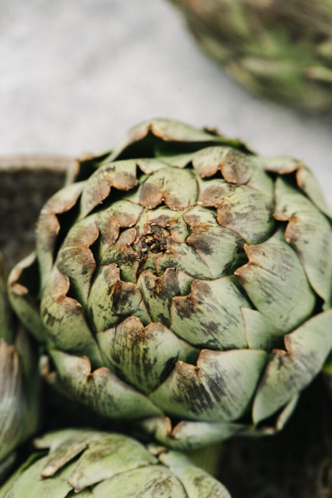 Side view, a whole artichoke in a brown bowl.