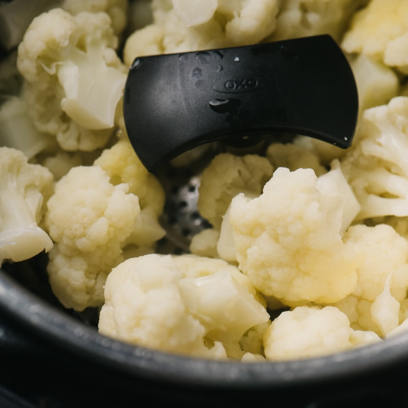 Side view, steamed cauliflower florets in a steamer basked in the inner pot of an Instant Pot.