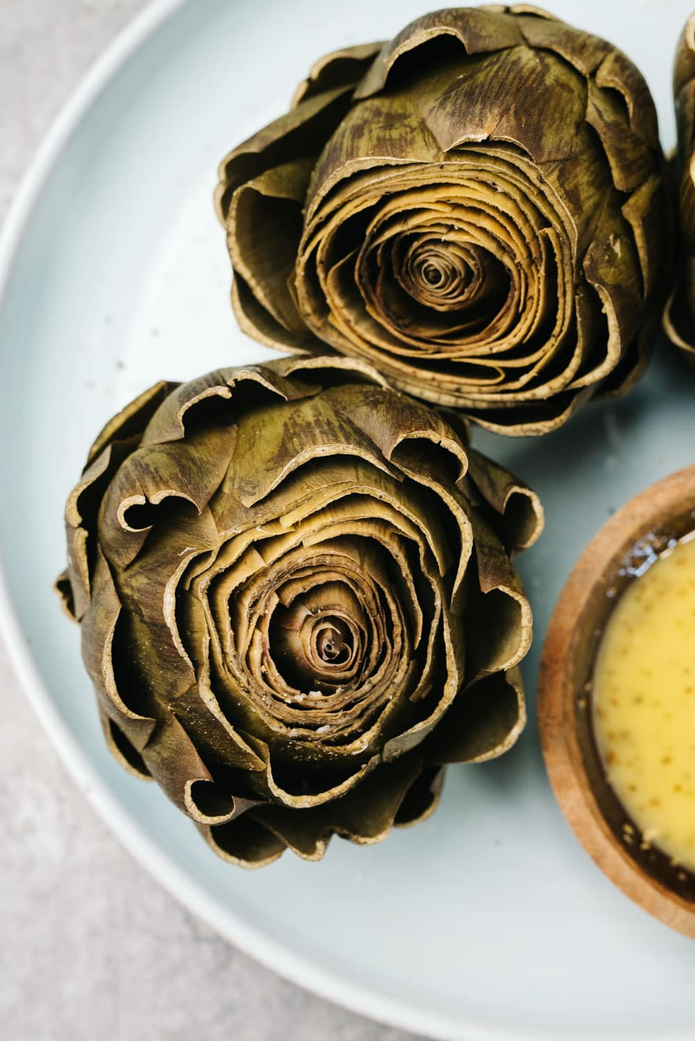 Two steamed artichokes cooked in the instant pot on a blue plate with a small bowl of lemon dipping sauce.