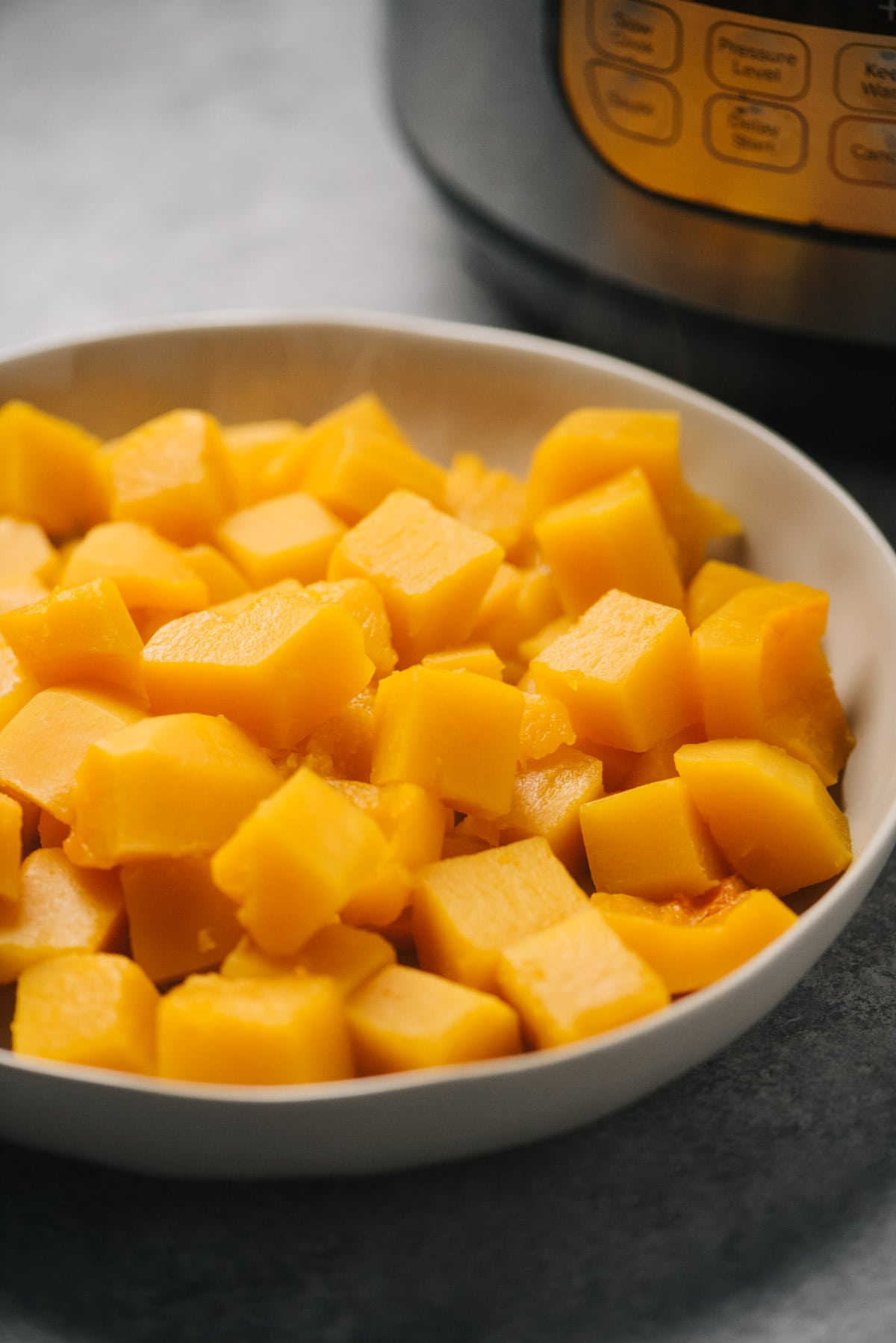 Side view, butternut squash cubes in a tan serving bowl in front of an Instant Pot.