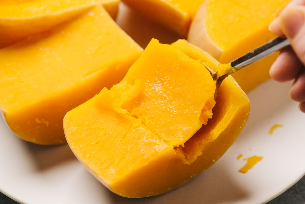 A spoon scooping the flesh from the skin of a cooked chunk of butternut squash.