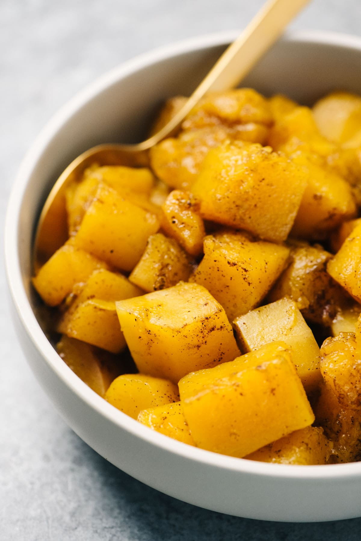 Diced and steamed instant pot butternut squash in a tan serving bowl, seasoned with spices, with a gold serving spoon.