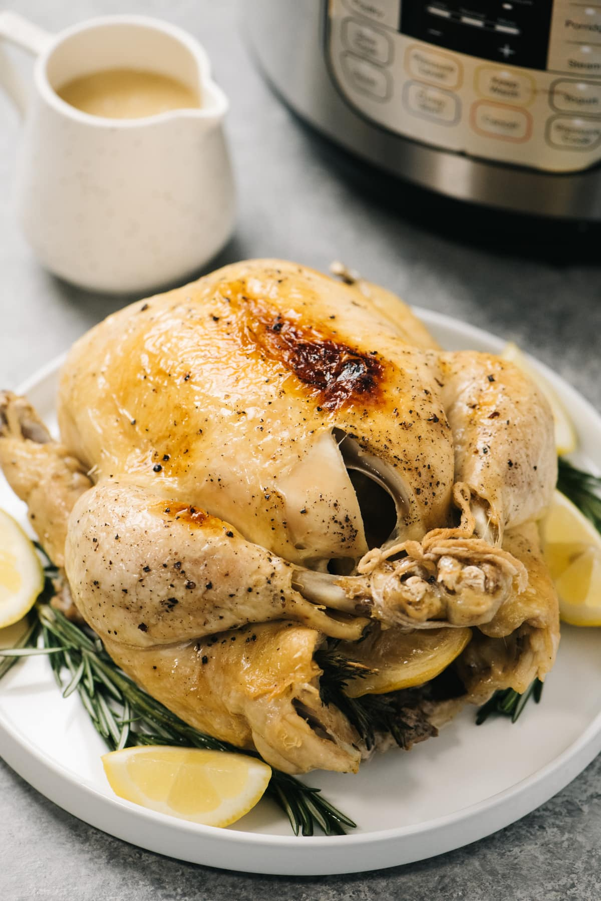 Side view, a whole instant pot chicken on a serving platter with a pitcher of gravy and a pressure cooker in the background.