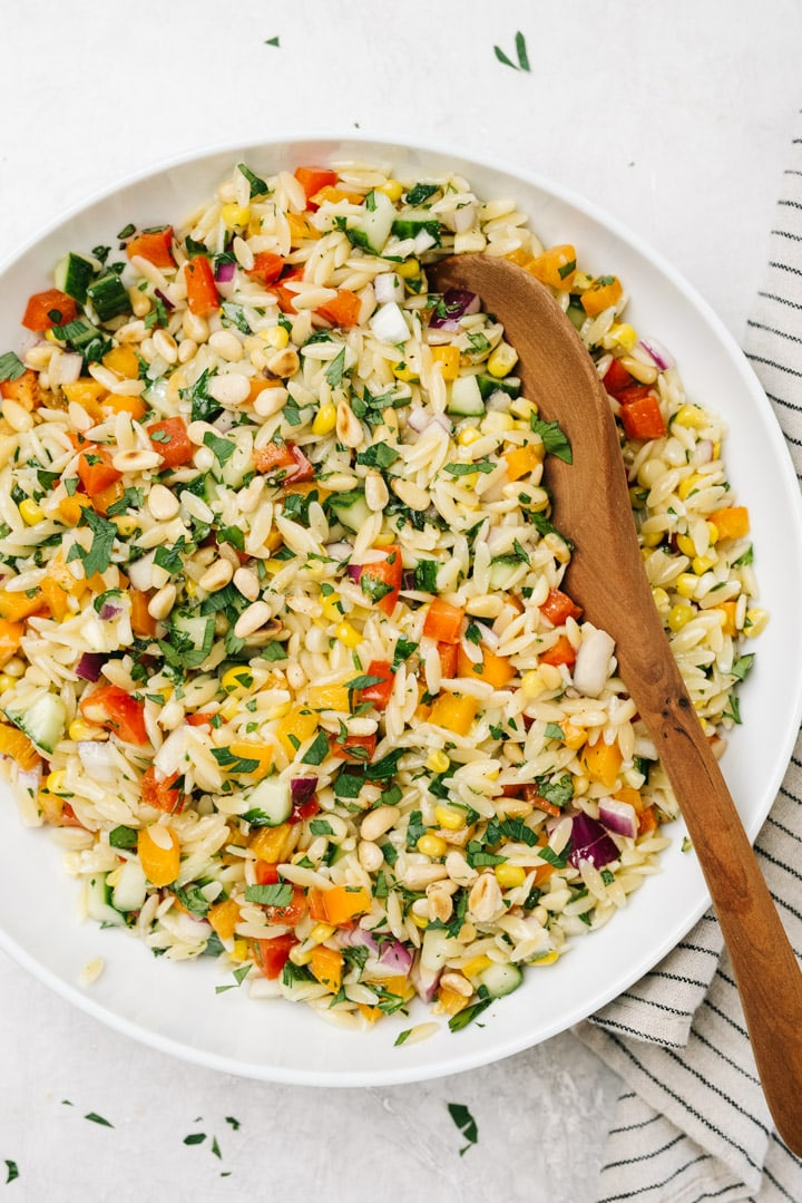 Mediterranean orzo salad in a white bowl with a wood serving spoon and striped linen napkin on a concrete background.