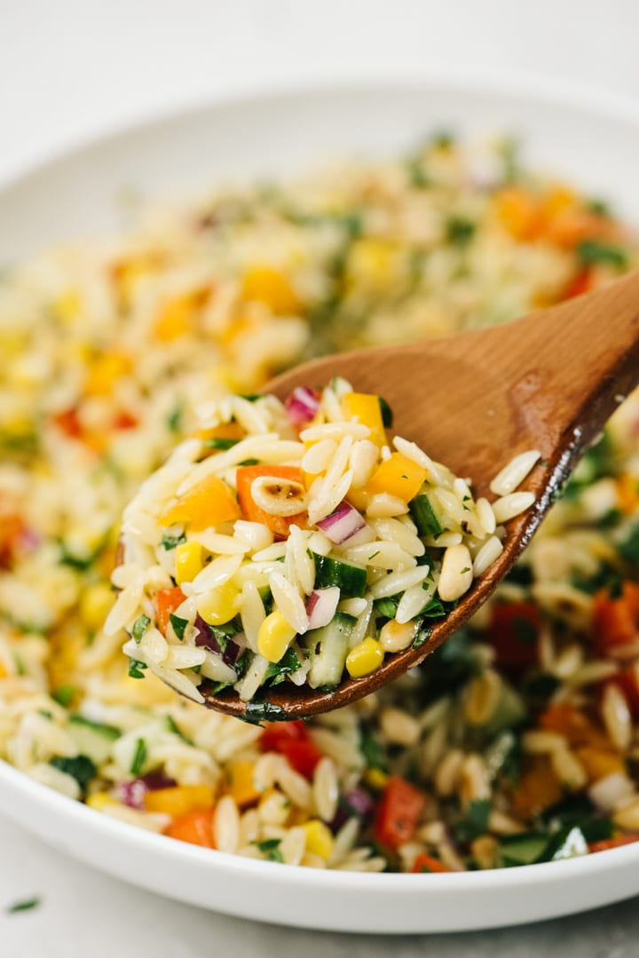Side view, a spoonful of orzo salad hovering over a serving bowl.