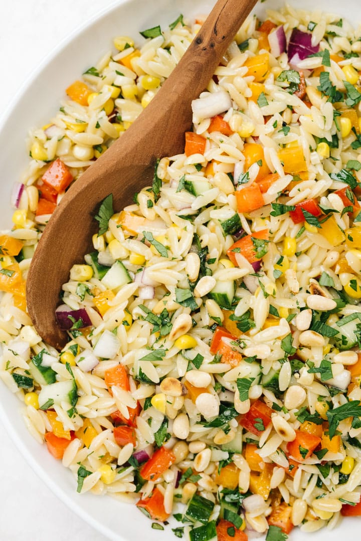 From overhead, a wood serving spoon tucked into a bowl of mediterranean orzo salad.