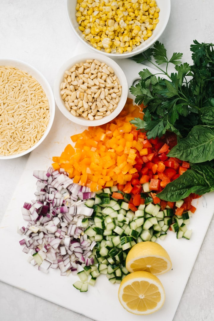 The ingredients for orzo salad arranged on a white cutting board.