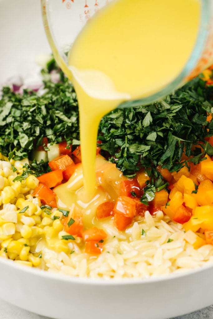 Pouring lemon vinaigrette over orzo salad with finely chopped herbs and vegetables.