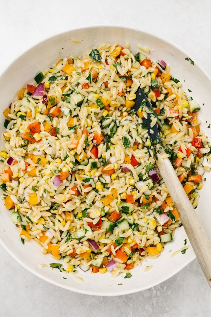 Orzo salad with vegetables, herbs, pine nuts, and lemon vinaigrette in a white serving bowl with a rubber spatula.