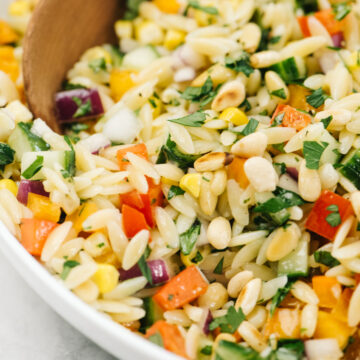Side view, a wood serving spoon tucked into a bowl of mediterranean orzo salad.