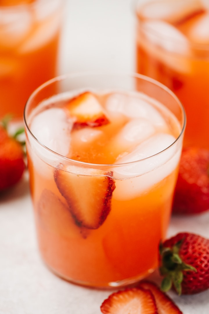 Three glasses of strawberry lemonade garnished with sliced strawberries on a concrete background.