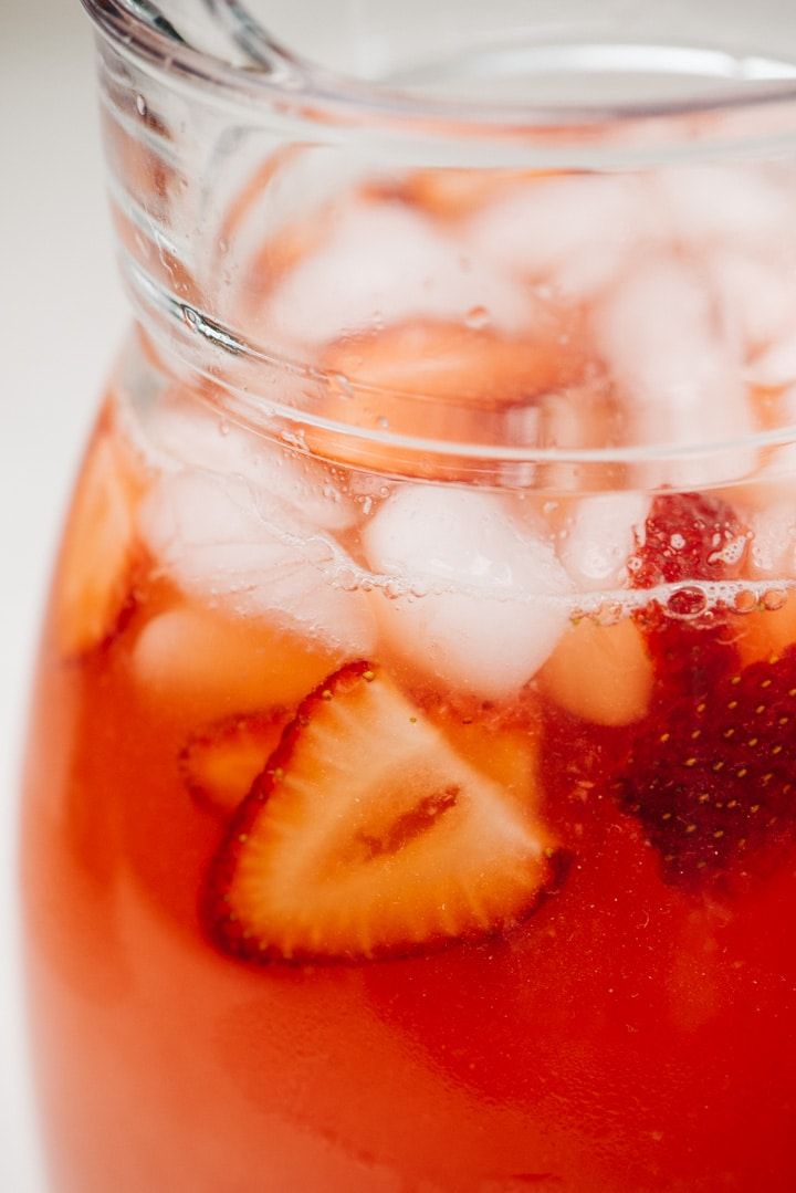 Side view, a pitcher of strawberry lemonade with ice and strawberry slices.