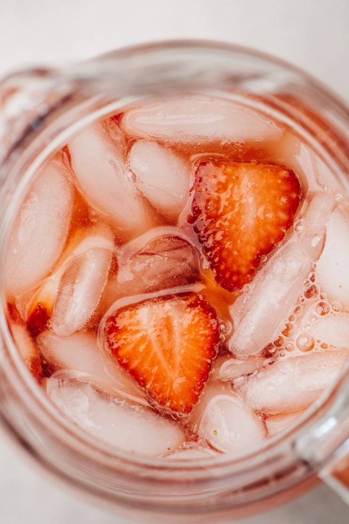 From overhead, a close up view of a pitcher of strawberry lemonade.