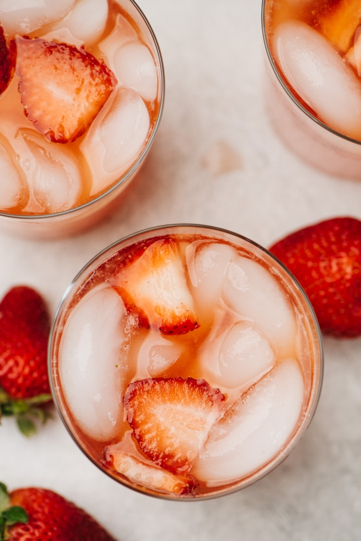 From overhead, three glasses of strawberry lemonade on a concrete background with several fresh strawberries scattered around the glasses.