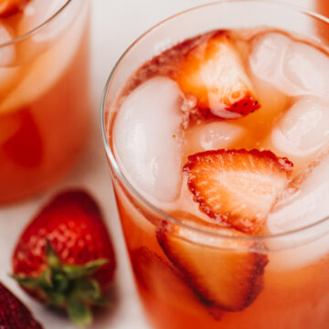 Two glasses of fresh strawberry lemonade on a concrete background with whole strawberries in the background.