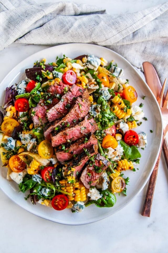 A steak dinner salad with grilled corn, blue cheese, and tomatoes on a white plate with rose gold silverware and a grey linen napkin.