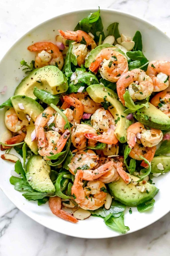 A citrus and avocado dinner salad with shrimp and greens in a large white serving bowl on a marble table.