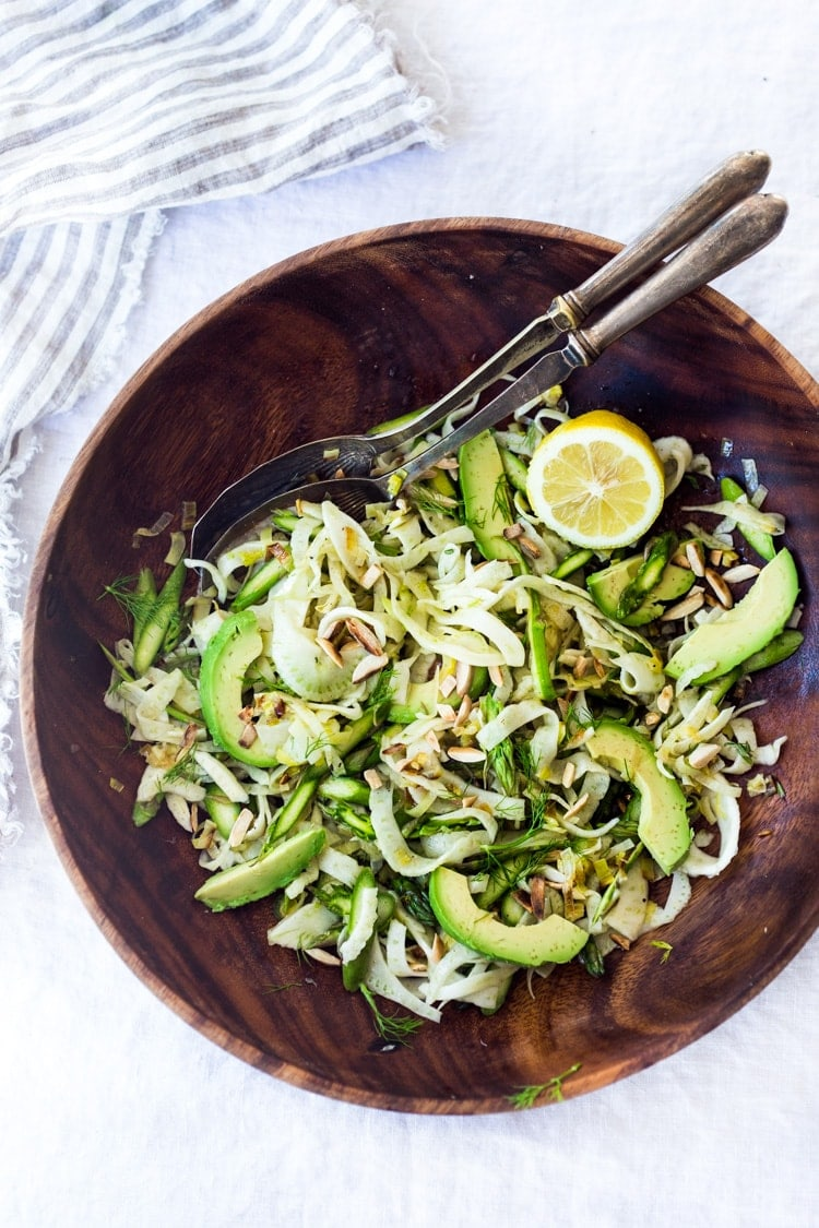 A fennel and avocado dinner salad in a brown serving bowl with serving utensils on a white linen background.