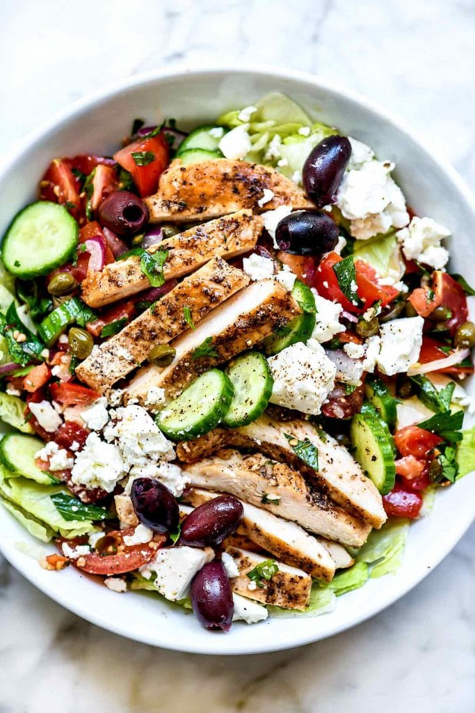 Greek dinner salad with feta, olives, and vegetables in a large white serving bowl on a marble table.