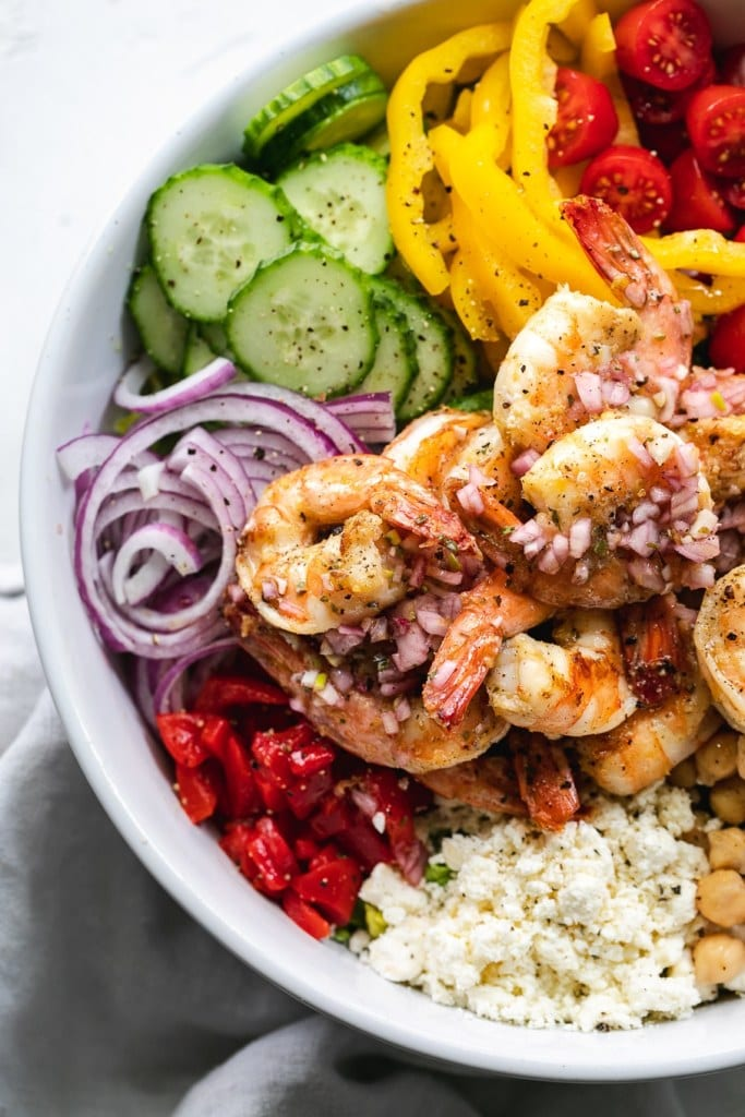 A mediterranean chopped salad with shrimp in a white bowl with a grey linen napkin.