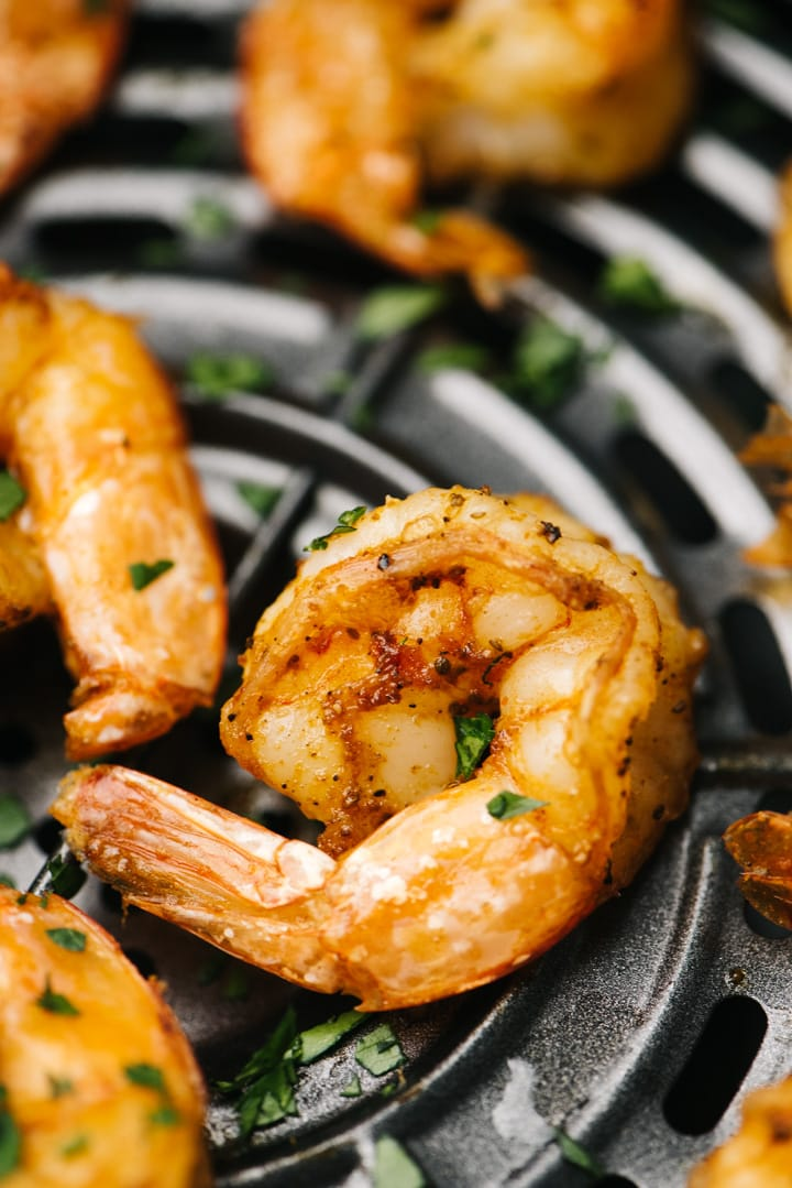 Side view, cook shrimp in the basket of an air fryer garnished with parsley.