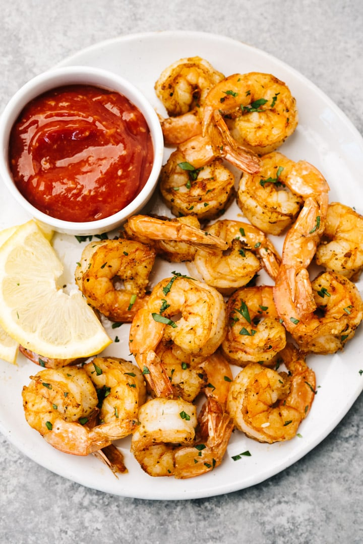 Air fryer shrimp on a white plate with lemon wedges and a bowl of cocktail sauce.
