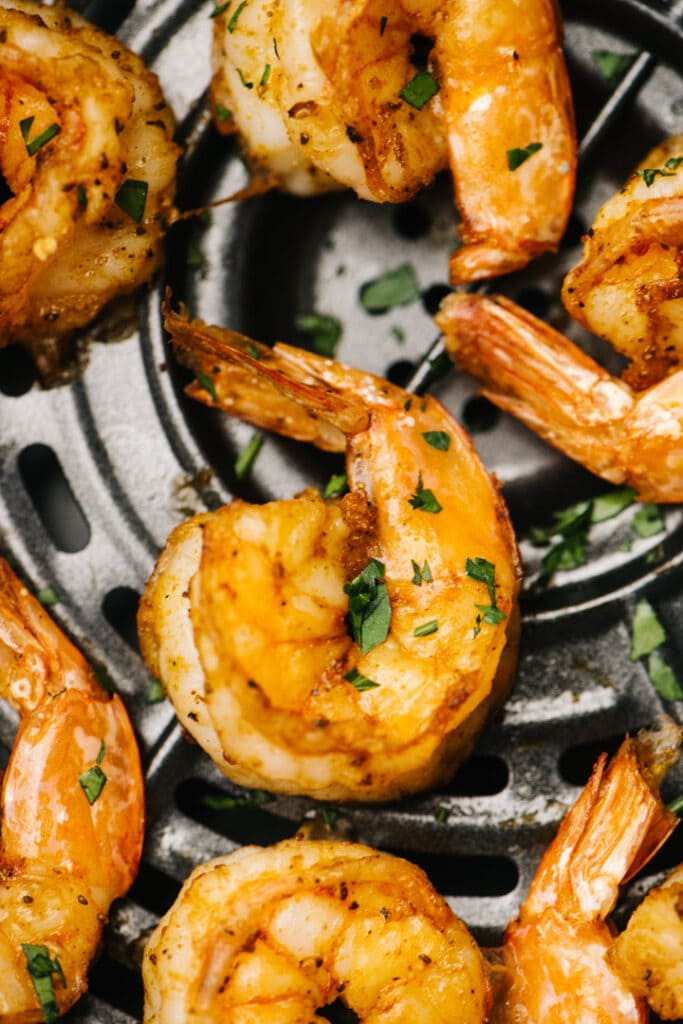 Cooked shrimp in the basket of an air fryer, garnished with parsley.