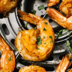 Air fryer shrimp garnished with fresh parsley.
