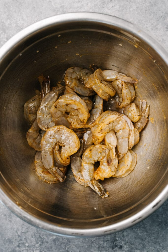 Raw shrimp tossed with old bay marinade in a metal mixing bowl.