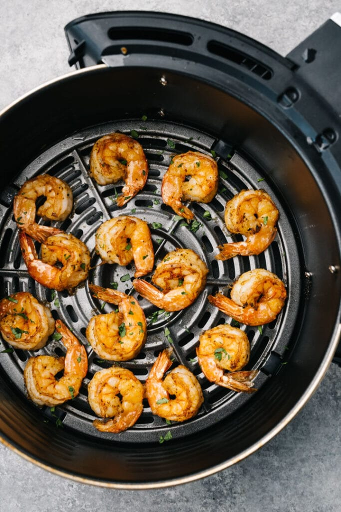Cooked shrimp in an air fryer in an even layer.