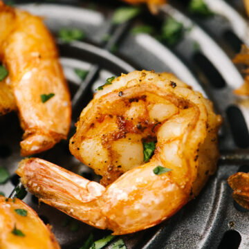 Side view, cooked shrimp in the basket of an air fryer garnished with parsley.