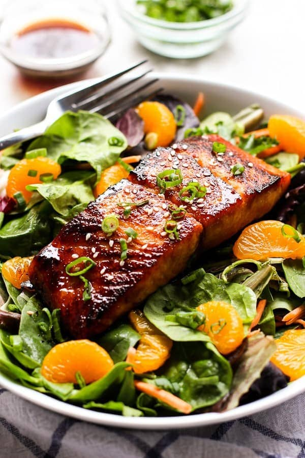 An asian salmon salad with mandarin oranges over greens in a white bowl with vinaigrette in the background.