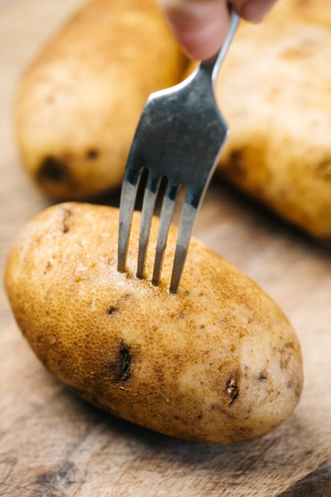 Using the tines of a fork to poke holes in a raw russet potato.