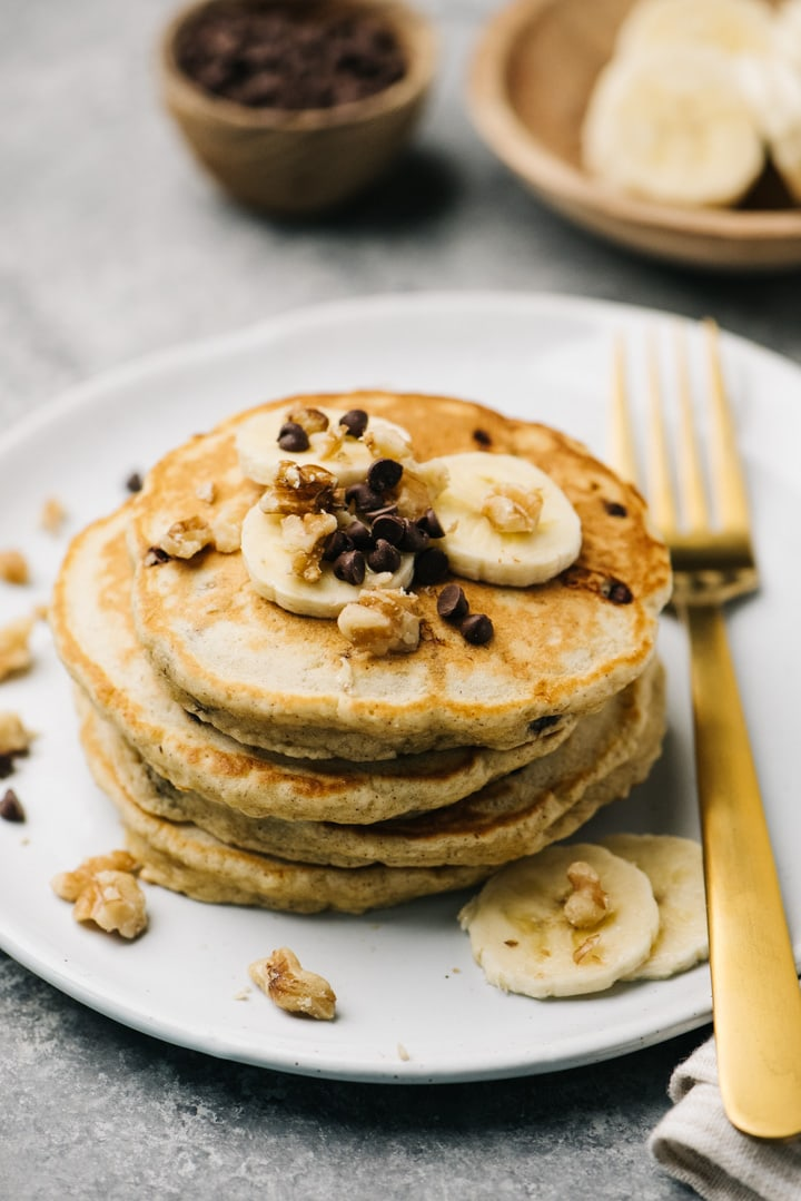 A stack of banana bread pancakes topped with bananas, walnuts, and chocolate chips.