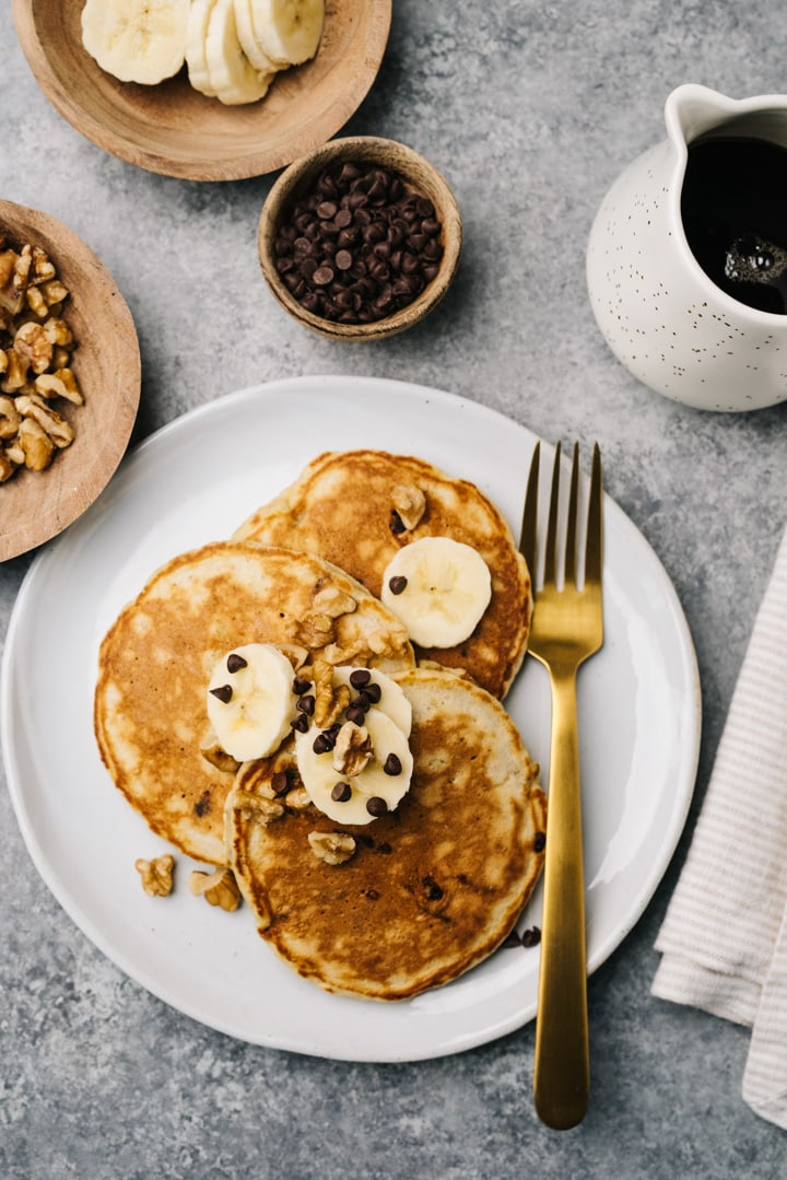 Three banana bread pancakes on a white plate with a fork, surrounded by garnish bowls of bananas, walnuts, mini chips, and a pitcher of maple syrup.