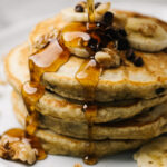 Pouring maple syrup onto a stack of banana bread pancakes, topped with sliced bananas, walnuts, and mini chocolate chips.