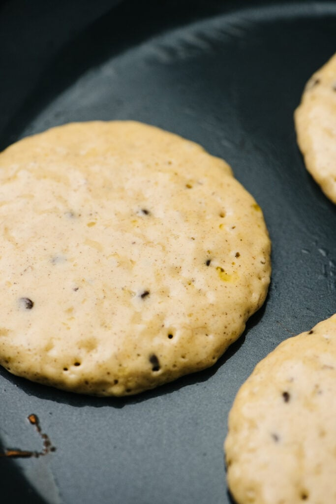 Side view, three pancakes in a skillet showing bubbles and set edges.
